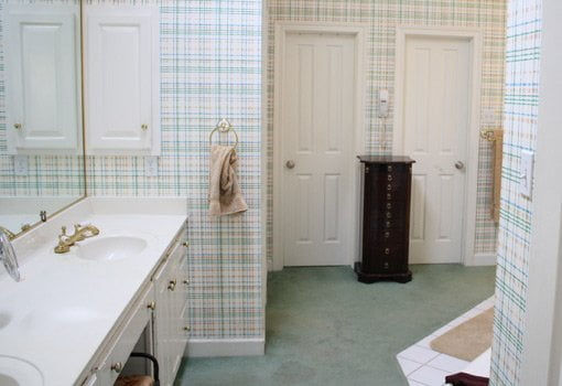 Bathroom before remodel with plaid wallpaper and carpet on the floor.