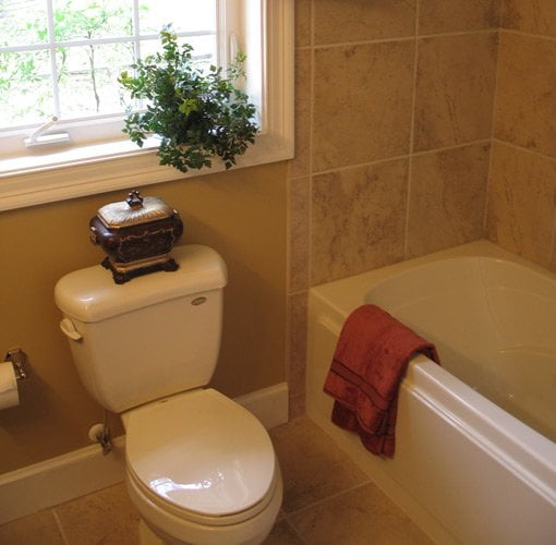 Bathroom after renovation with new tile, tub, and toilet.