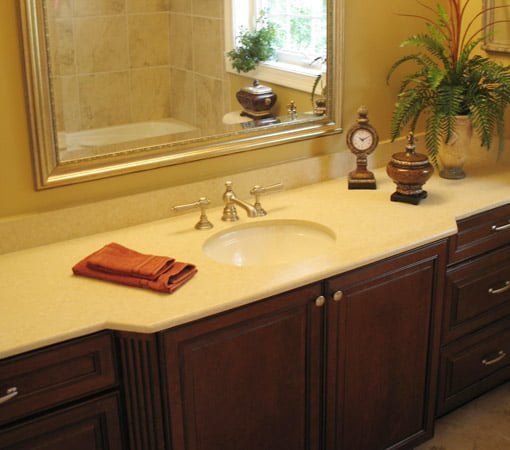 Remodeled bathroom with stained wood cabinet and solid surface countertop.