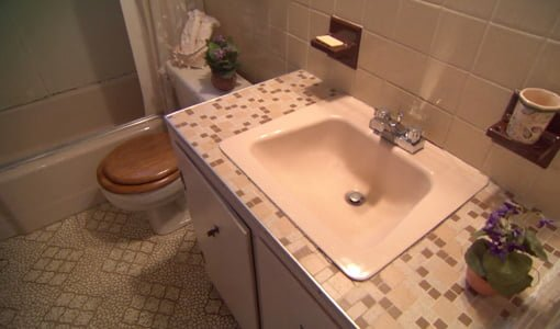 Bathroom with tile countertop and vinyl floor before remodeling.
