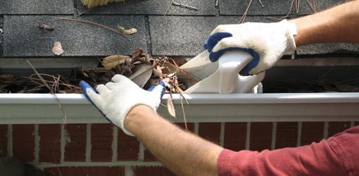 Using homemade scoop from plastic container to remove leaves from gutter.