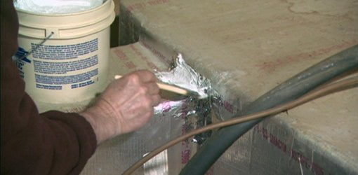 Using metallic tape and duct mastic to repair gaps in heating ductwork.