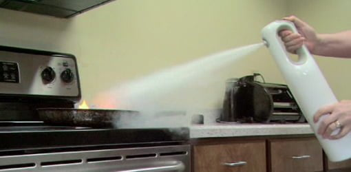 Using a fire extinguisher to put out a fire on a stove.