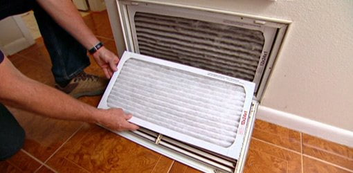 Replacing the air filter on a central heating/cooling air return.