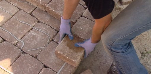 Using polyurethane construction adhesive to secure dry stacked stones in place.