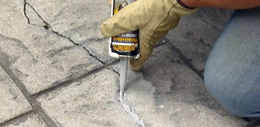 Beau Applying Concrete Caulk To Crack In Patio.