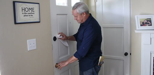 Danny Lipford lubricating a door lock.