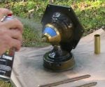 Spray painting an outdoor brass light fixture.