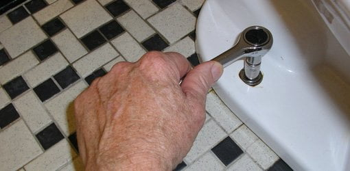 Using socket wrench to remove nuts on toilet flange bolts.