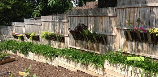 Fence built on sloping ground with planters.