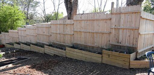 Raised bed planters used to fill the gaps at the bottom of the fence above.