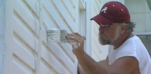 Painting wood siding on home.
