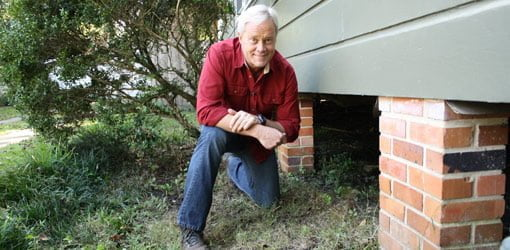 Danny Lipford kneeling next to crawlspace