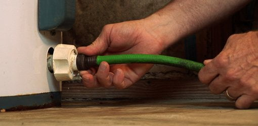 Attaching garden hose to drain valve on hot water heater.