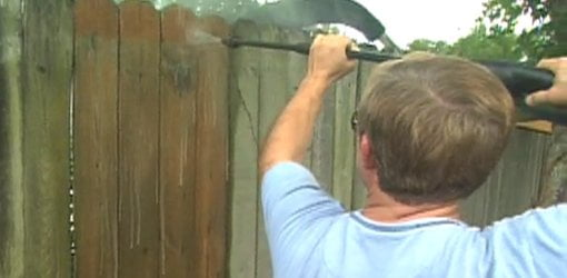 Using a pressure washer to clean a wood fence.