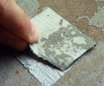 Pulling duct tape off a concrete surface.