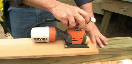 Using an orbital sander to sand wood.