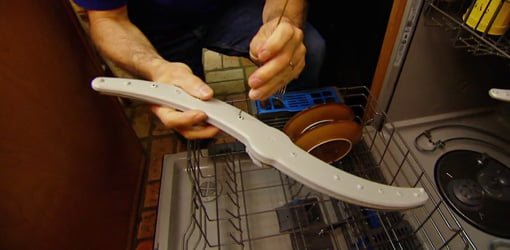 Using wire from a coat hanger to clean the holes on dishwasher spray arms.