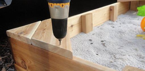 Using screws to attach sandbox seat.