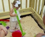 Child playing in competed wood deck sandbox.