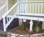 Wood porch with white railings, gray flooring, plumb steps, and yellow-green siding.