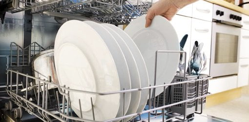 Loading plates in a dishwasher.