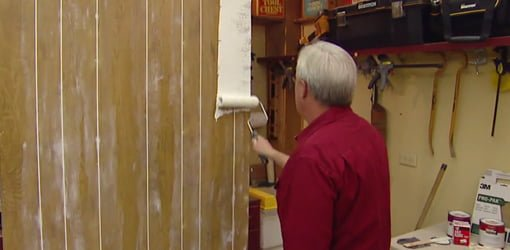Danny Lipford priming wall paneling with a paint roller.