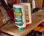 Glue bottle stored upside down in hole drilled in workshop shelf..
