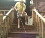Using a pressure washer to clean the steps on a wood deck.