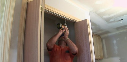 Man with cordless drill Installing track for bifold closet doors.