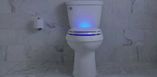 Toilet with blue light illumination in seat.