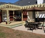 Wood deck with shade arbor pergola and concrete patio on back of brick house.