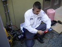 HVAC professional working on air conditioner unit outdoors.