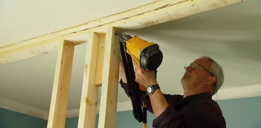 Using a pneumatic nailer to  frame up an interior wall.