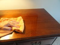 Using cloth to wax table top.