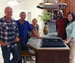 Today's Homeowner crew and contest winners standing around kitchen island with new Broan range hood.