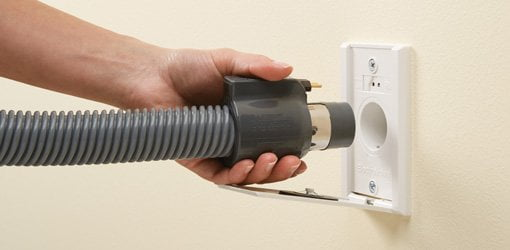 Attaching hose to wall outlet of NuTone central vacuum system.