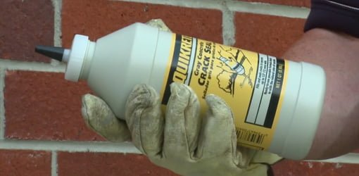 Gloved hand holding bottle of QUIKRETE Concrete Crack Seal.