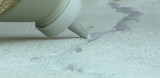 Filling crack in concrete with crack sealant.