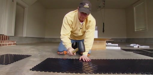 Using A Rubber Mallet To Install Interlocking Tiles On Garage Floor