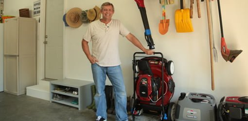 Man in garage with garden tool rack and Toro SmartStow lawn mower.