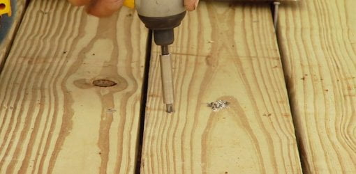Using a drill to attach pressure treated wood deck boards.