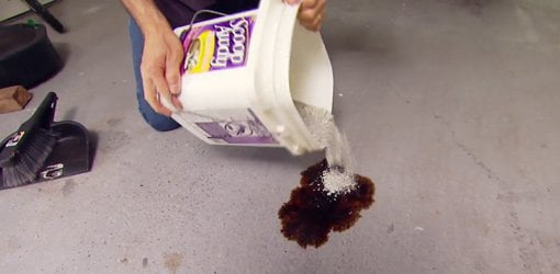 Pouring kitty litter on oil on a concrete garage floor.
