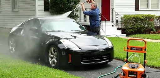Man using a pressure washer to clean a black sports car in driveway.