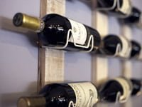 Wall-mounted wine rack with bottles of wine.