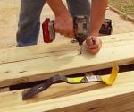 Using a cordless drill and deck screws to attach new wood decking.