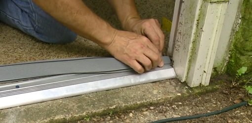 Inserting rubber seal into new entry door threshold.