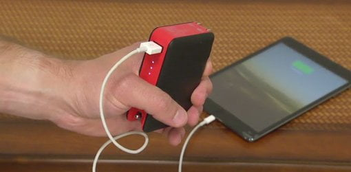 Hand holding Transit myCharge portable battery recharger plugged into smartphone.