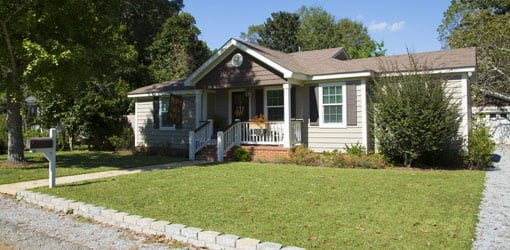 Single story ranch house with almond colored vinyl siding, brown shutters, and white trim.