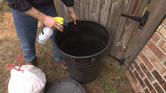 spraying trash can with ammonia